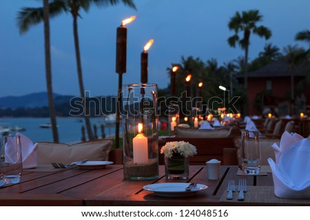 Outdoor restaurant tables, dinner setting on the beach at evening - stock photo
