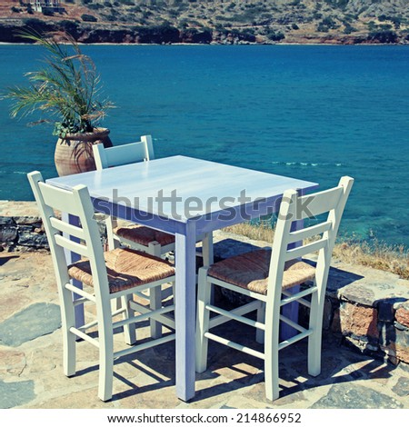 Outdoor restaurant - traditional greek tavern with lilac table and white chairs overlooking Mediterranean sea (Crete, Greece ). instagram effect, square image - stock photo