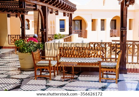 Outdoor seating area with modern wooden furniture on a patio at luxury holiday apartments or hotel