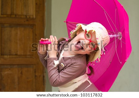Outdoor shoot of small girl with umbrella. - stock photo