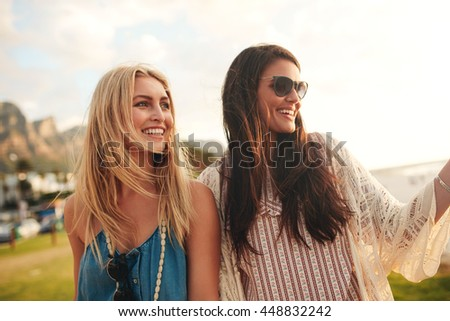 Outdoor shot of cheerful young female friends together on a beach. Two attractive women enjoying a holiday on the sea shore. - stock photo