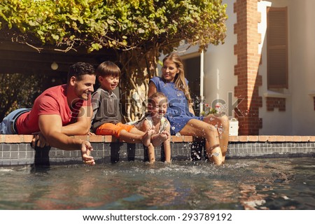 Outdoor shot of happy young family splashing water with hands and legs while sitting on edge of swimming pool. Family enjoying a hot sunny day playing by the pool. - stock photo