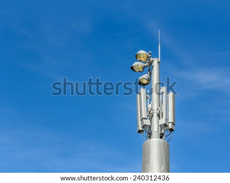 Outdoor stadium lights and telecommunication tower against daytime blue sky. Single row of bulbs with cell phone gsm antennas on tall metal pole. Room for text, copy space. Blue sky, wispy clouds.  - stock photo