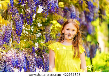 Outdoor stylish portrait of a cute little girl of 8-9 years old, standing next to beautiful purple wisteria flowers, wearing green blouse - stock photo