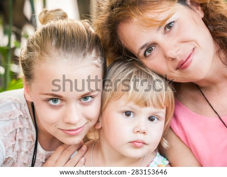 Outdoor summer closeup portrait of a real Caucasian family, young mother with her two daughters - stock photo