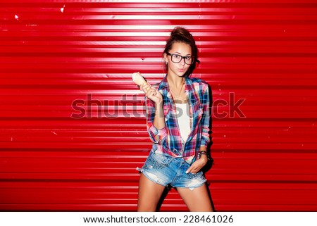 Outdoor summer colorful fashion closeup portrait of young pretty smiling crazy girl with ice-cream on red wall background  - stock photo
