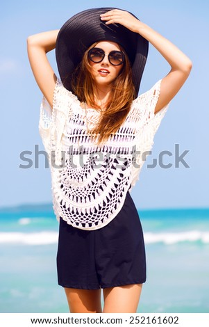 Outdoor summer fashion portrait of beautiful elegant woman wearing luxury vintage hat and boho chic outfit, posing at windy sunny day at tropical beach, amazing view to the ocean. - stock photo