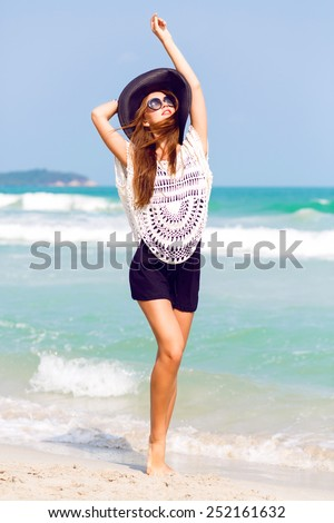 Outdoor summer fashion portrait of beautiful elegant woman with perfect body and long legs wearing hat and boho chic outfit, posing at windy sunny day at tropical beach, amazing view to the ocean. - stock photo