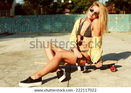 Outdoor summer hot portrait of pretty blond sensual sexy girl in bikini sitting on the beach