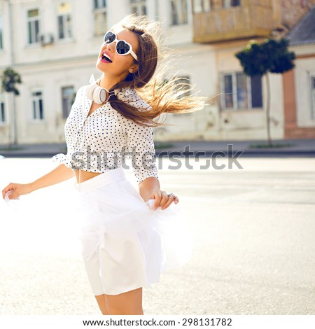 Outdoor summer lifestyle image of young pretty hipster woman having fun, listening music and dancing on the street, city center Europe, cute white vintage outfit and sunglasses, fun ,joy, emotions. - stock photo