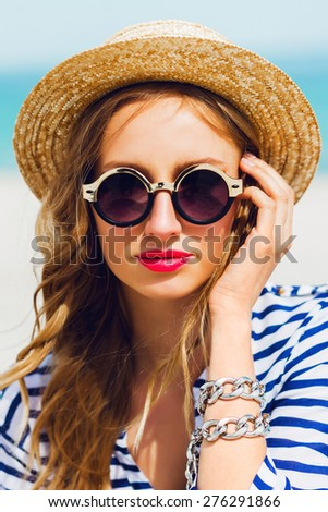 Outdoor summer lifestyle  portrait of pretty blonde stylish woman in straw hat  and sunglasses. Have bright mace up and wearing striped shirt. enjoying  her summer vacations. - stock photo