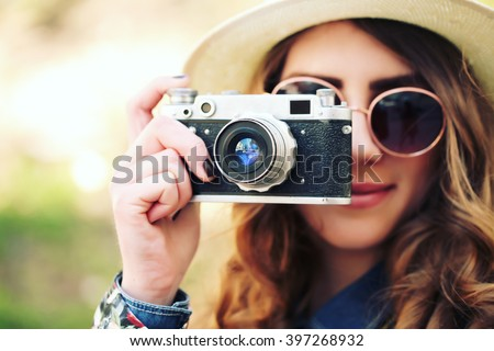 Outdoor summer lifestyle portrait of pretty young woman having fun in the city. Photographer making pictures in hipster style glasses and hat. Photo toned style Instagram filters. - stock photo