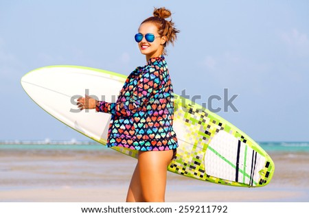 Outdoor summer portrait of sexy smiling woman running with surfer board near blue ocean,  wearing bright neon clothes and sunglasses, have fit tanned body and ginger hairs. - stock photo