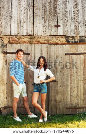 Outdoor summer portrait of young beautiful couple having fun on countryside together - stock photo