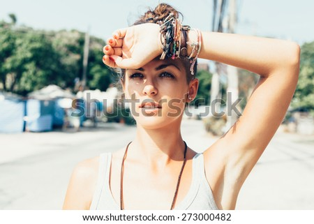 Outdoor summer portrait of young pretty cute brunette girl. Beautiful woman posing at street in hot day.  - stock photo