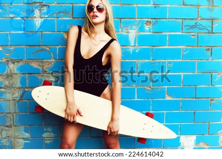 Outdoor summer portrait of young pretty sexy sport style blonde woman in blue pool with big longboard desk and have fun alone in hot weather  - stock photo