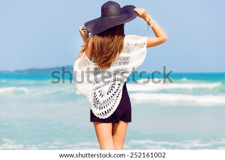 Outdoor summer portrait of young pretty woman looking to the ocean at tropical beach, enjoy her freedom and fresh air, wearing stylish hat and clothes. - stock photo