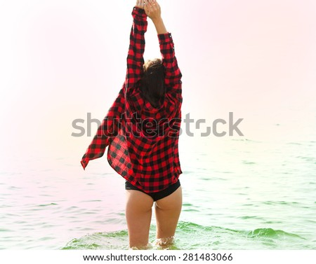 Outdoor summer portrait of young pretty woman looking to the sea at beach,enjoy her freedom and put her hands up in the air,wearing stylish summer clothes. - stock photo