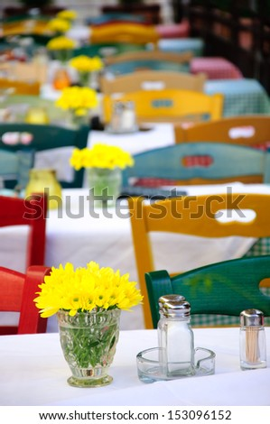 Outdoor summer restaurant tables and chairs with yellow flowers in vases - stock photo