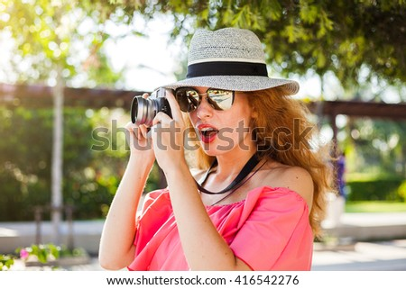 Outdoor summer smiling lifestyle portrait of pretty young redhead woman having fun in the city in Europe with camera travel photo of photographer Making pictures in hipster style glasses and hat - stock photo