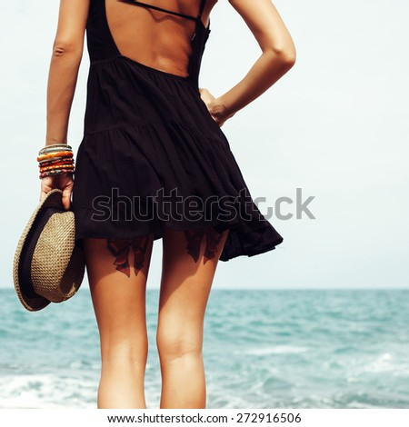Outdoor summer sunny fashion portrait of pretty young sensual blonde woman posing in black dress on the rocks on the ocean seashore. Outdoors lifestyle portrait - stock photo