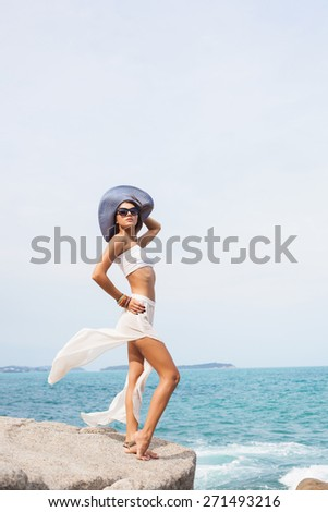Outdoor summer sunny fashion portrait of pretty young sensual woman posing in hat and black dress on the rocks and have fun alone on the ocean seashore. Outdoors lifestyle portrait - stock photo