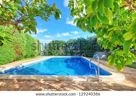 Outdoor swimming pool with blue water near the garden. - stock photo