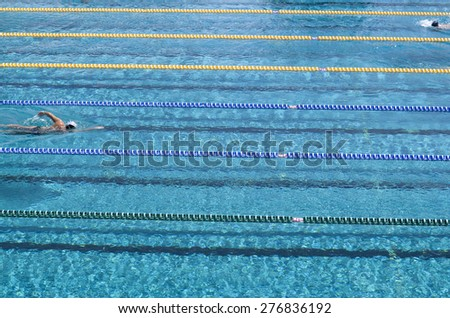 Outdoor swimming pool with  swimmers in sunny day