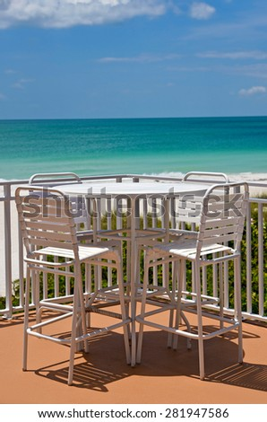 Outdoor Table and Chairs on a Patio overlooking white sandy beach on the Gulf of Mexico - stock photo