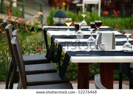 outdoor table with served plate and wine glasses - stock photo