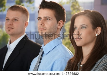 Outdoor team portrait of determined and young businesspeople. - stock photo