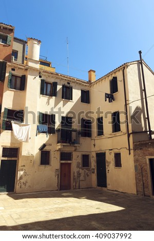 outdoor view of traditional Italian small courtyard. medieval architecture village. white wall with windows, wooden door and balcony. Tuscany ancient house  - stock photo