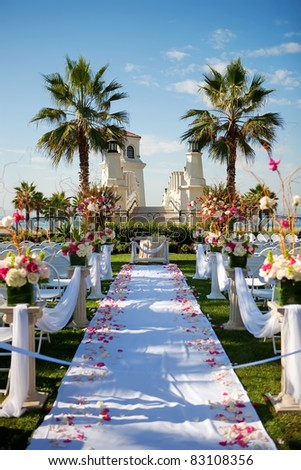 Outdoor wedding by the beach with palm trees, rose petals on isl - stock photo