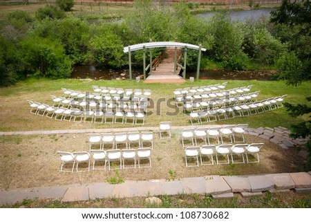 outdoor wedding ceremony with white chairs - stock photo