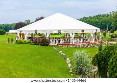 Outdoor wedding reception in tent - stock photo