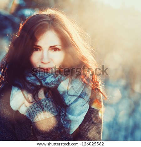 Outdoor winter closeup colorful portrait of young happy brunette. Girl in winter coat in sunshine - stock photo