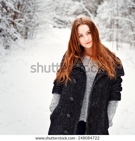 Outdoor winter cold weather portrait of pretty young smiling woman posing in grey coat and sweater  - stock photo