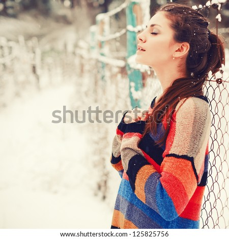Outdoor winter portrait of young sensual brunette in color sweater - stock photo