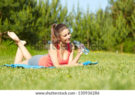 Outdoor workout woman. Fitness woman runner relaxing drinking water after training outside in  park