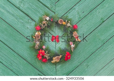Outdoor X-mas wreath from fir tree branches at old rustic door background - stock photo