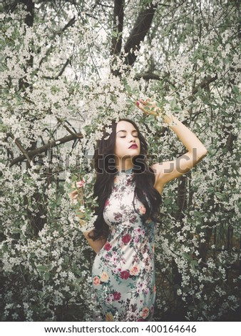 Outdoors fashion photo of beautiful young lady in the garden of cherry blossoms - stock photo