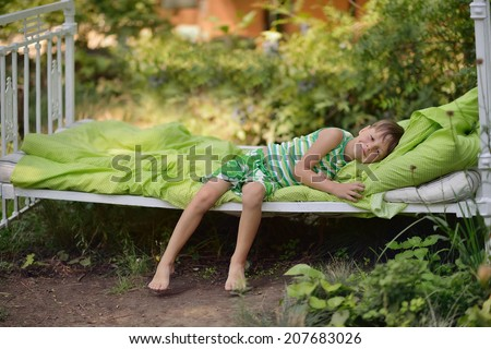 Outdoors in the green stands the white bed with a little cute boy - stock photo