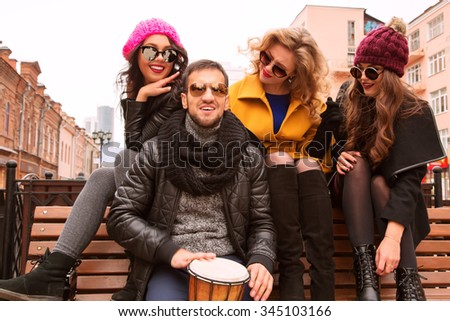 Outdoors lifestyle fashion portrait of cheerful company of friends sitting on the bench. Handsome guy playing the drum. Three pretty girls singing and having fun. Wearing stylish outerwear, sunglasses - stock photo