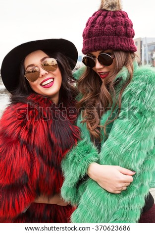 Outdoors lifestyle fashion portrait of two pretty cheerful girls best friends in stylish hats and  fur coats. Smiling and walking on the city. Wearing stylish colored outerwear with sunglasses. - stock photo