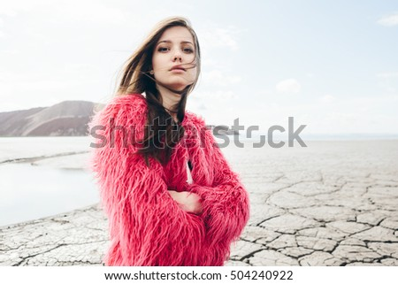 Outdoors lifestyle portrait of fashion girl in desert dry land