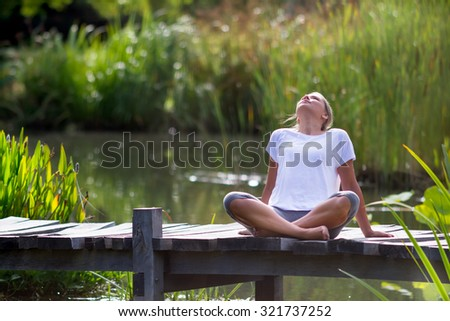 outdoors meditation - beautiful young yoga woman enjoying to relax on a wooden bridge with green foreground and water background, summer daylight - stock photo