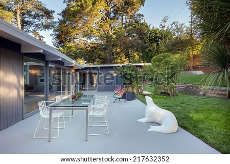 Outdoors of modernist villa in Mid century home style with seating arrangement. - stock photo
