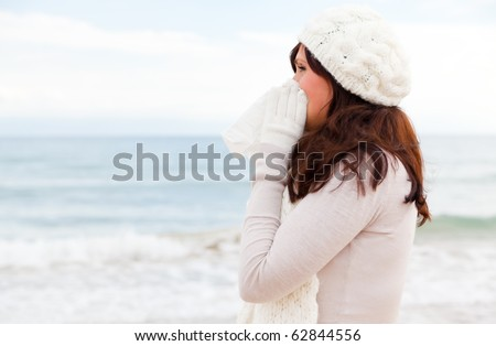outdoors on the beach standing female sneezing in tissue wearing scarf and warm clothes feeling sick
