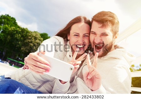 outdoors photo of joyous couple showing peace sign and taking selfie by mobilephone - stock photo