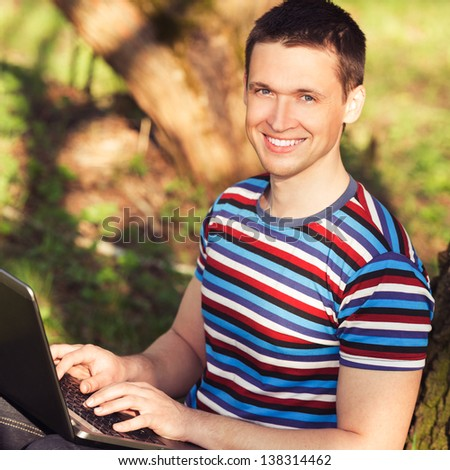 outdoors portrait men with laptop in sunny day in park - stock photo